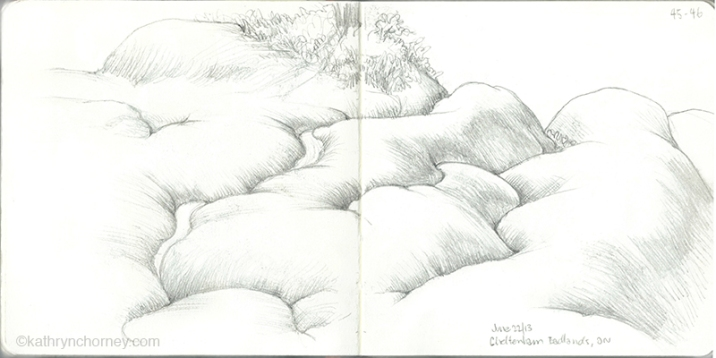 A sketch without colour focuses on the folding, intersecting forms of the badland hills.